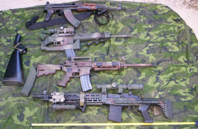 "Pictured are from top to bottom: 7.62x39S AKMS. 5.56 Keltec SU16C, 5.56 16"" M-4, 7.62x51N M1A SOCOM w/ Sage EBR stock"